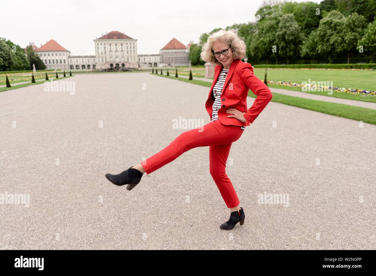 buoyant senior woman (67 years old) shaking leg outdoors in park next to touristic sight Schloss Nymphenburg, in Nymphenburg, Munich, Germany. - Stock Image