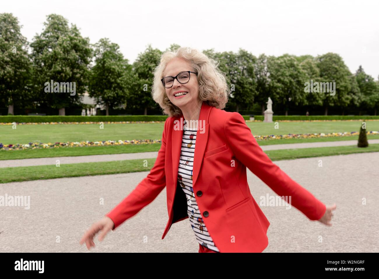 happy senior woman (67 years old) walking in park, in Nymphenburg, Munich, Germany. - Stock Image