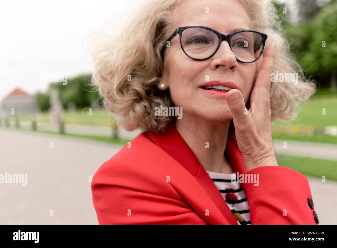senior woman (67 years old) touching her head in park, in Nymphenburg, Munich, Germany. - Stock Image