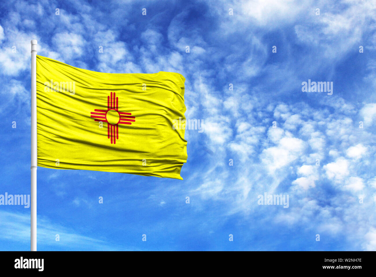 National flag State of New Mexico on a flagpole in front of blue sky - Stock Image