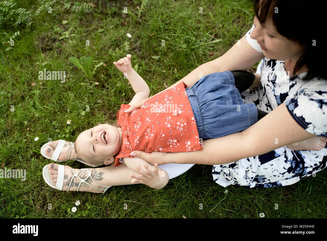 middle-aged grandmother playing with granddaughter baby toddler outdoors on meadow in park Stock Photo