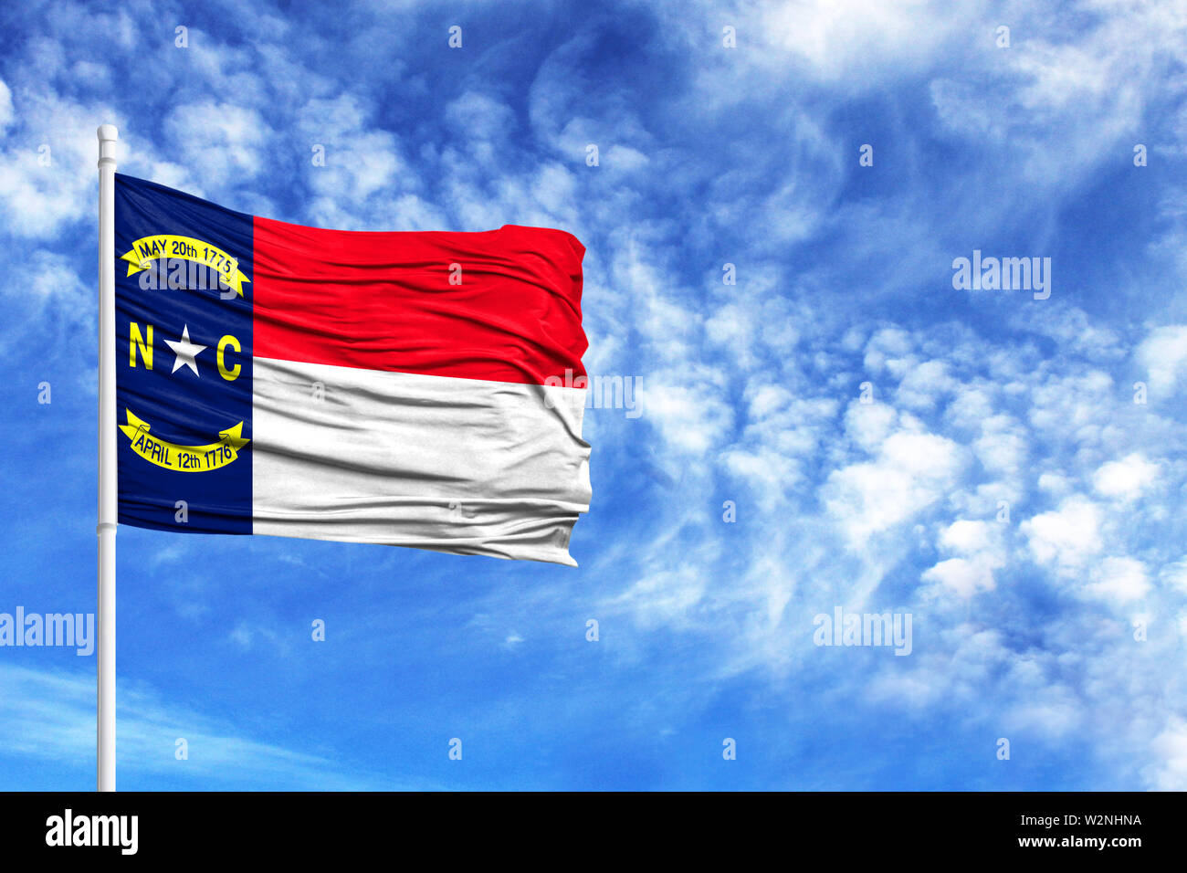 National flag State of North Carolina on a flagpole in front of blue sky - Stock Image