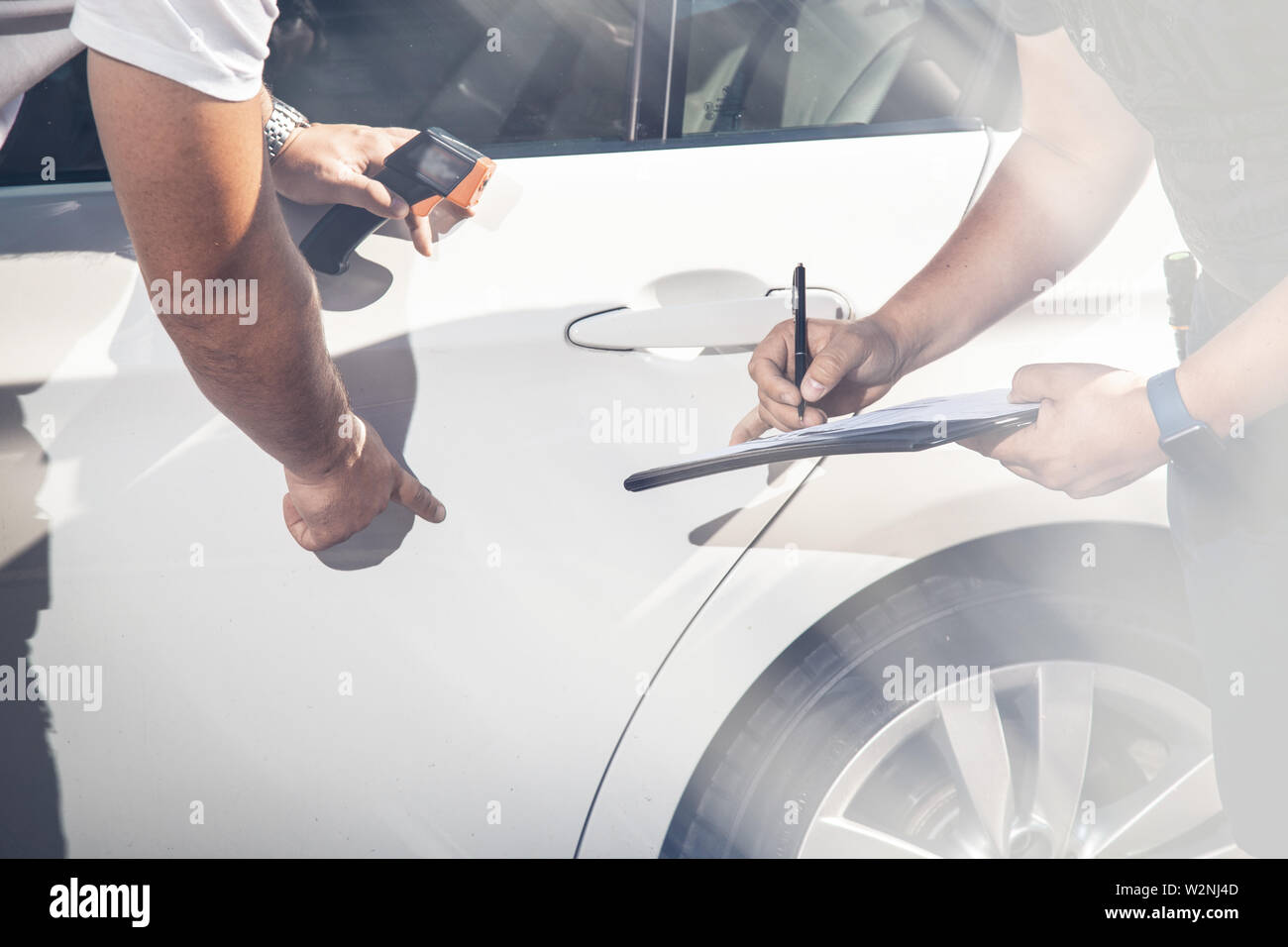 Against the background of a white car, inspectors inspect the transport vehicle, record defects. Stock Photo