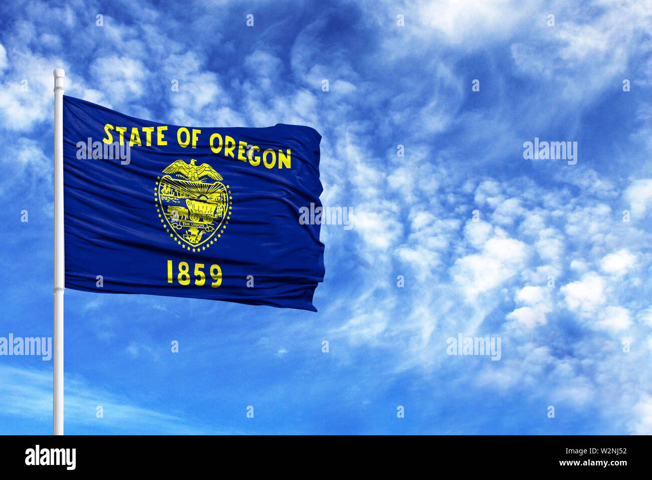 National flag State of Oregon on a flagpole in front of blue sky - Stock Image