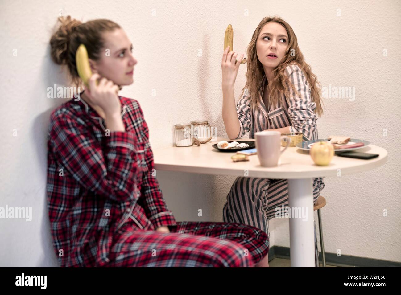 young annoyed women in pyjamas holding healthy bananas at breakfast table in shared student flat - Stock Image