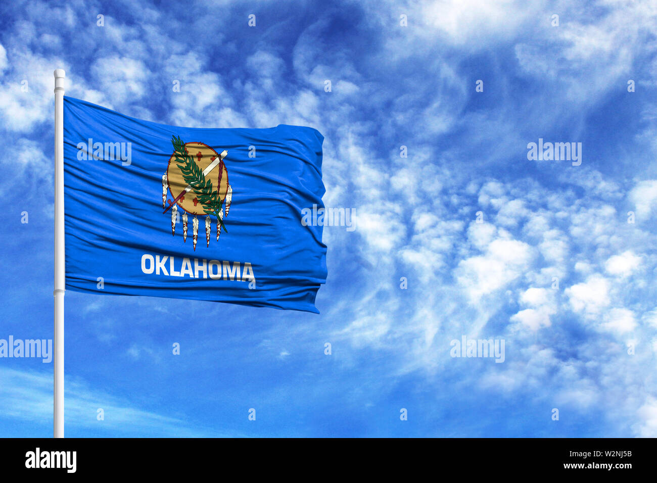 National flag State of Oklahoma on a flagpole in front of blue sky - Stock Image