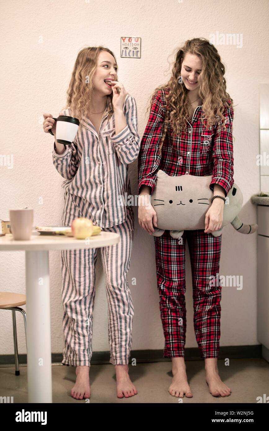 two friends in pyjamas starting day in student flat, morning - Stock Image