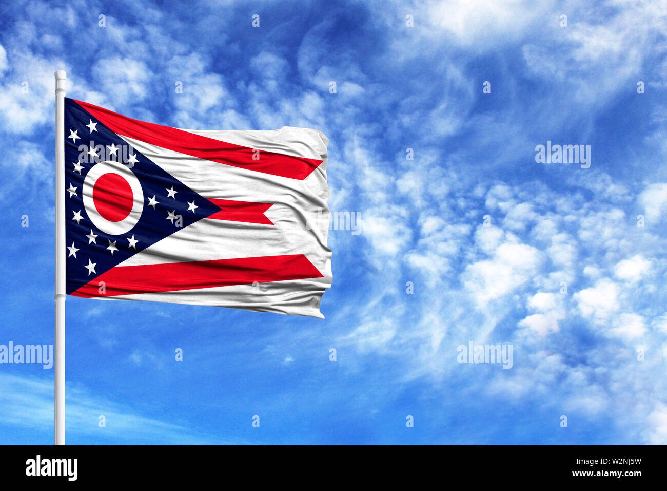 National flag State of Ohio on a flagpole in front of blue sky - Stock Image