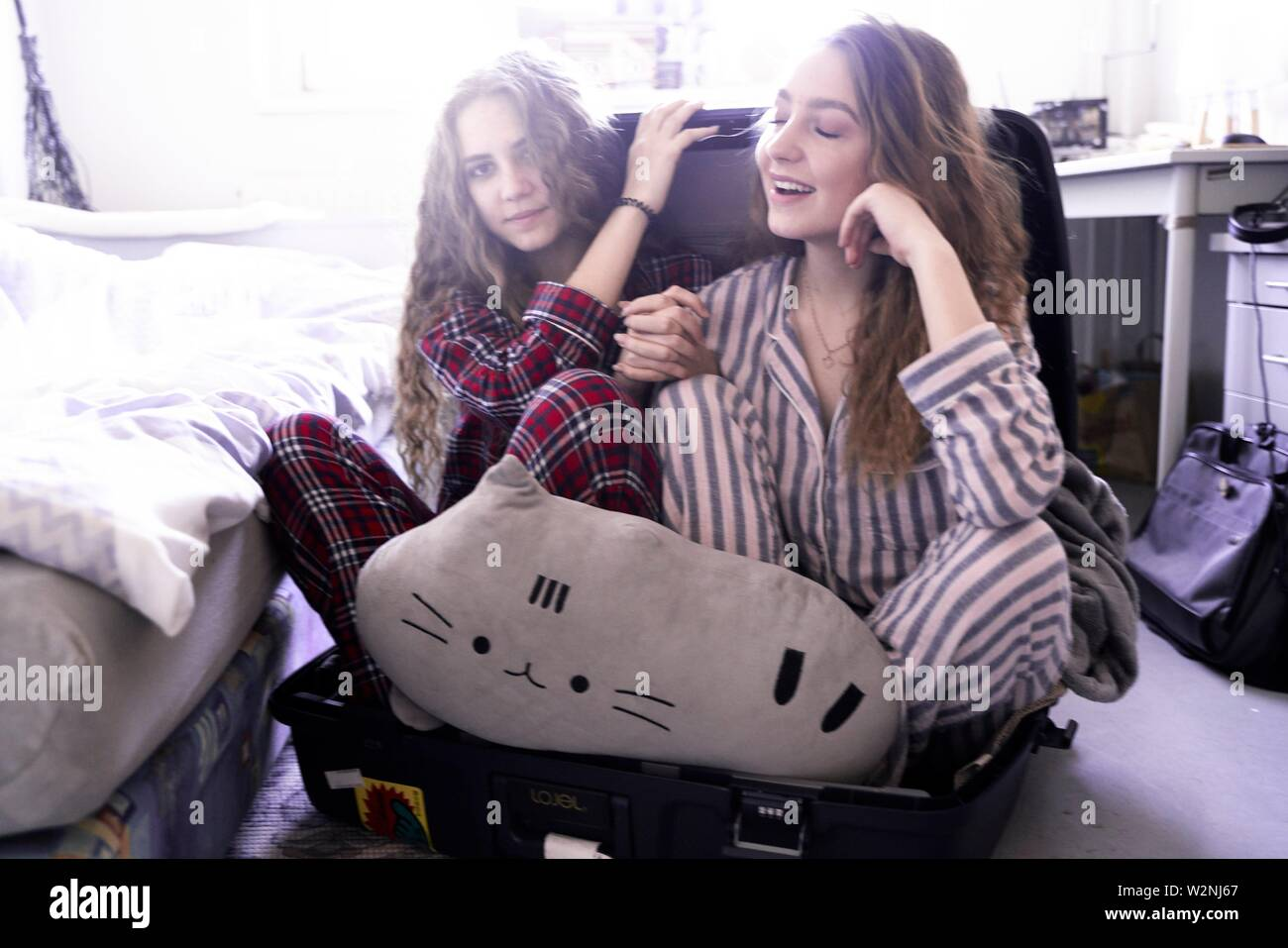 two young women wearing pyjamas and sitting in travel suitcase in bedroom - Stock Image