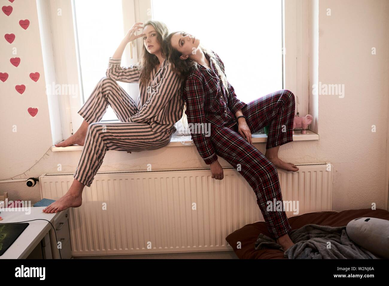 two young women in pyjamas sitting at windowsill in shared bedroom - Stock Image