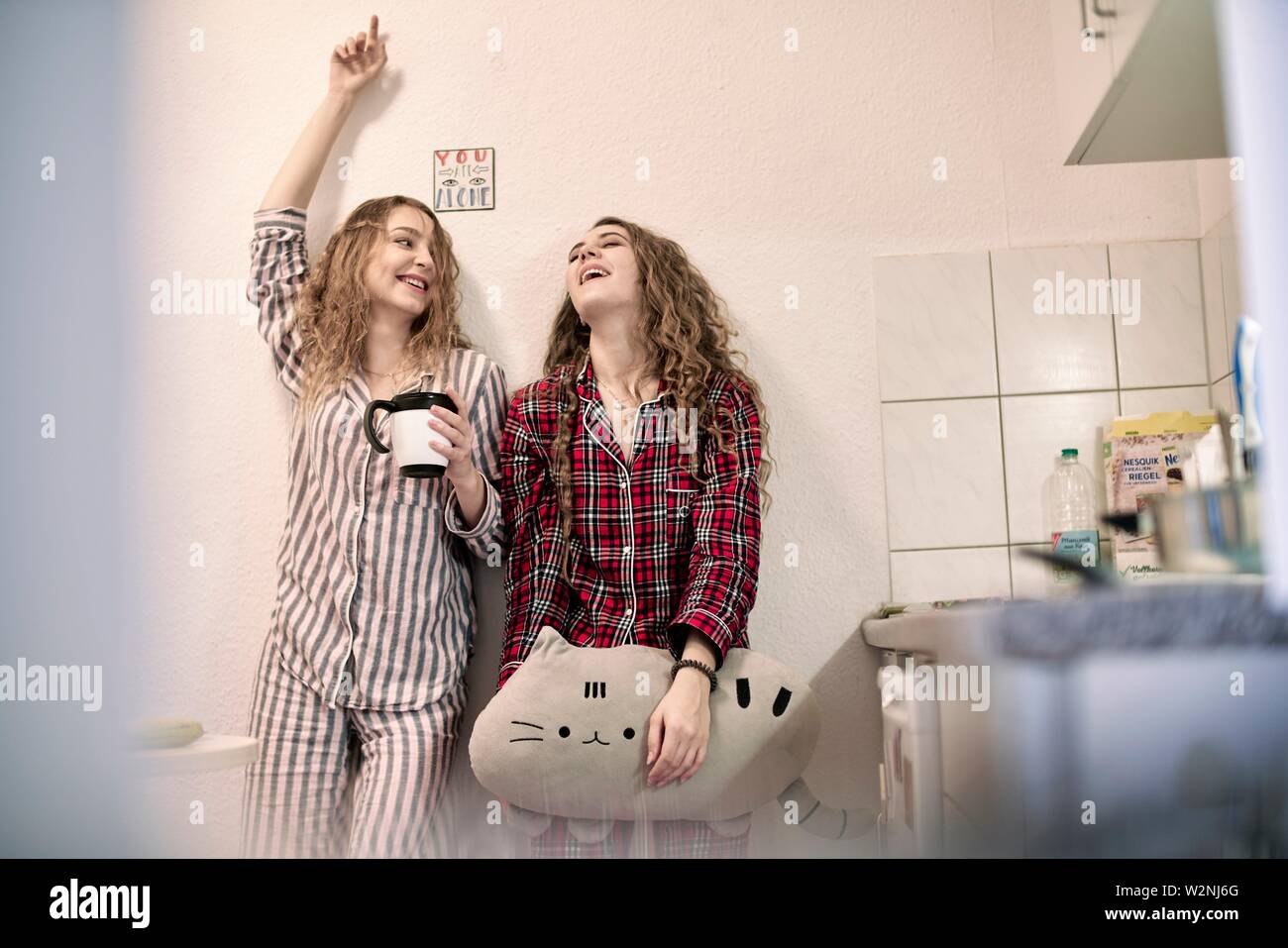 two women in pyjamas starting day in student flat, morning motivation - Stock Image