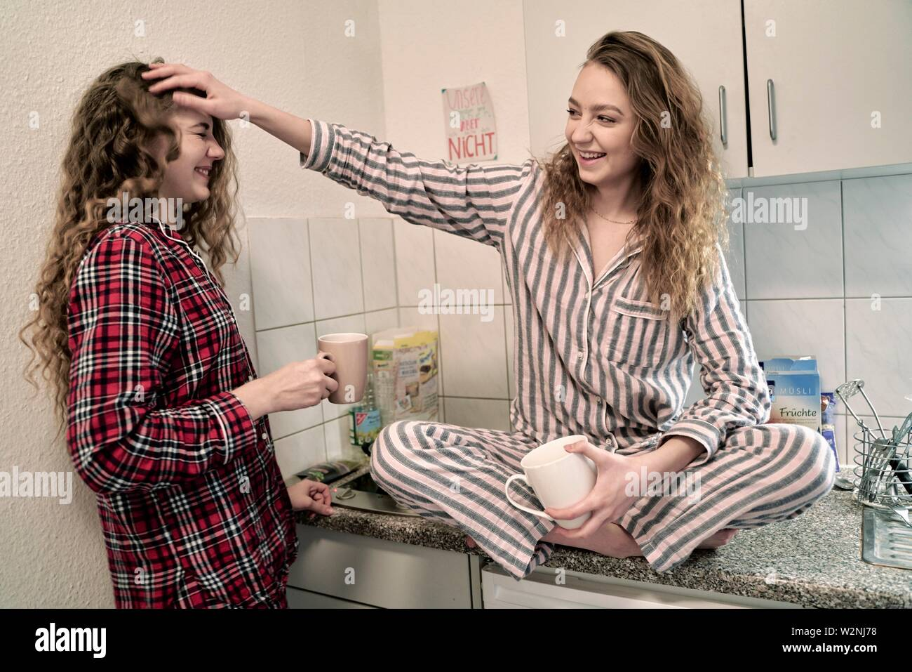 two young women wearing pyjamas in kitchen at home - Stock Image