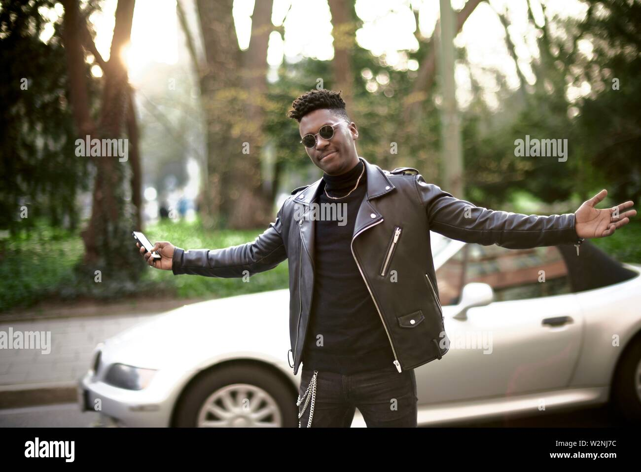 young African man shrugging shoulders at street, in Munich, Germany - Stock Image
