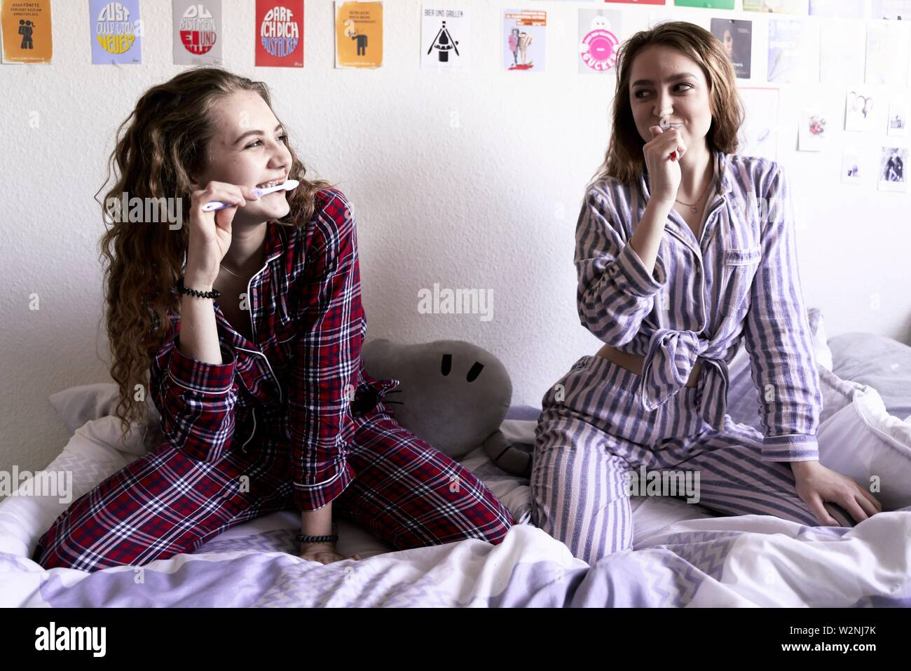 two young women in pyjamas brushing teeth while sitting on bed in bedroom - Stock Image