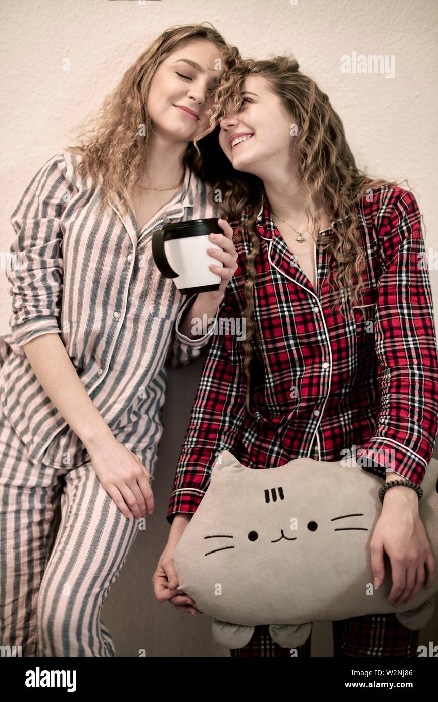 two tired friends in pyjamas with plushie and cup of tea - Stock Image