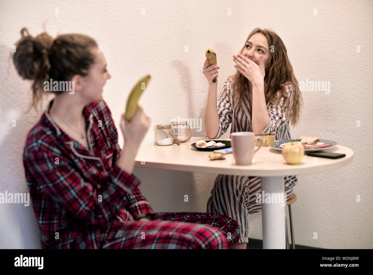 young women in pyjamas sitting at breakfast table in shared student flat, holding healthy bananas - Stock Image