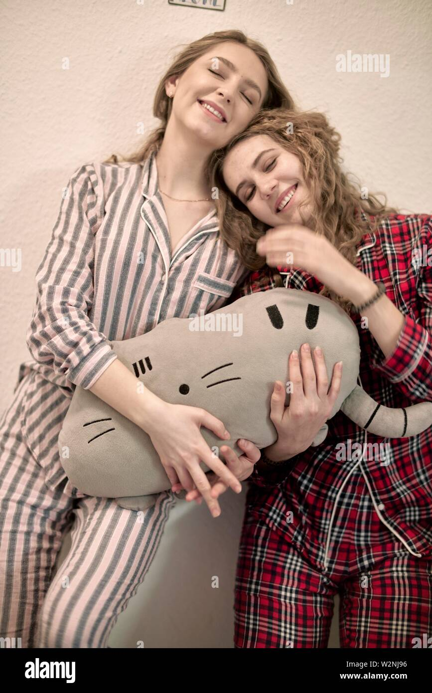 two friends in pyjamas with plushie - Stock Image