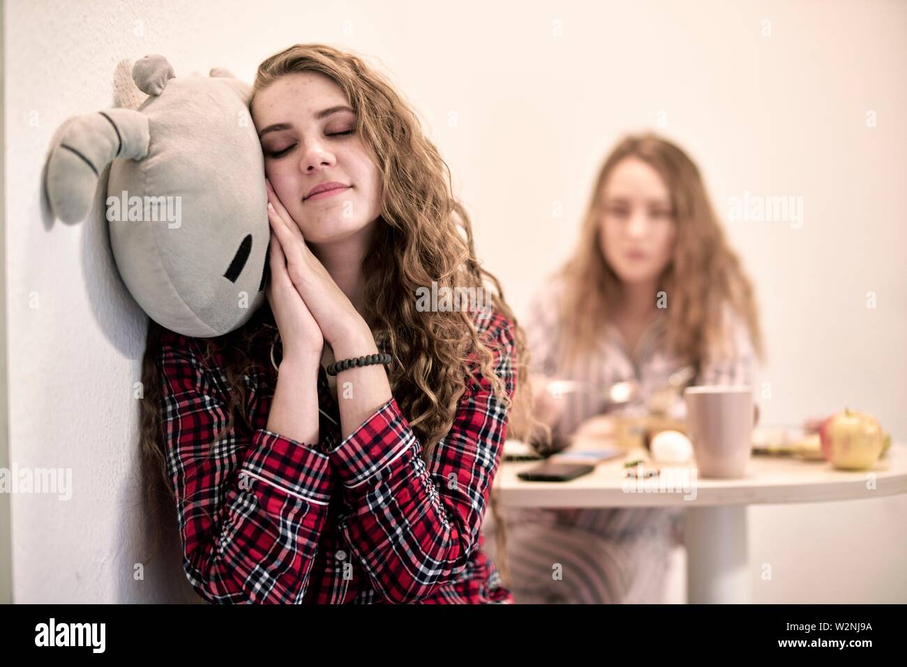 tired woman cuddling with plushie at breakfast table in morning, starting day in shared student flat - Stock Image