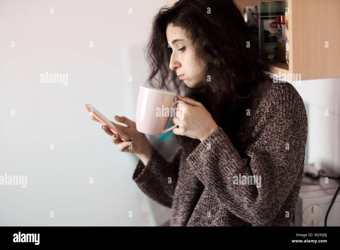 young woman using smartphone in morning - Stock Image
