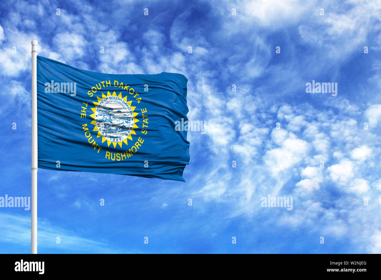 National flag State of South Dakota on a flagpole in front of blue sky - Stock Image