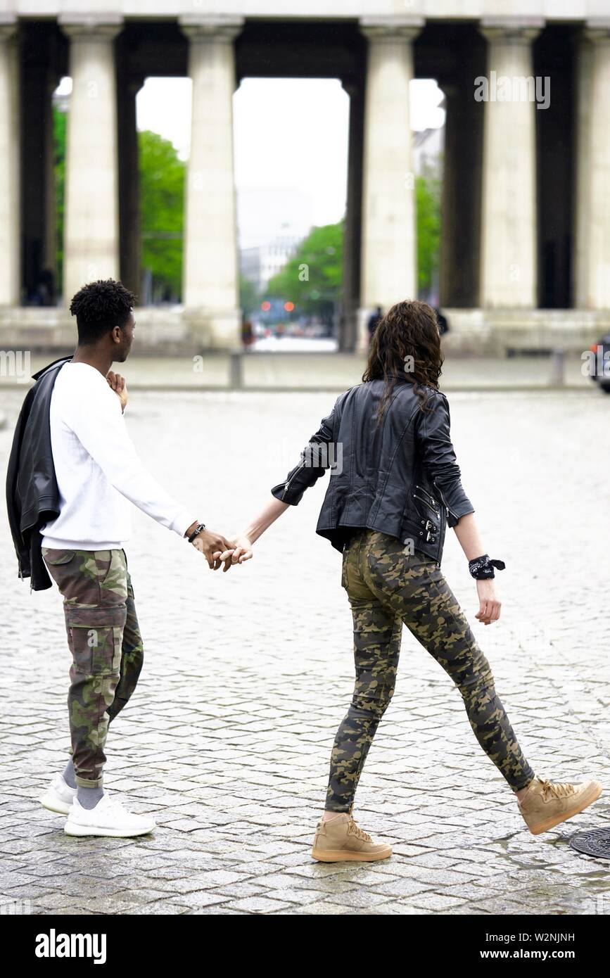 young mixed race couple crossing street in city, holding hands, in front of historical landmark Königsplatz, in Munich, Germany Stock Photo