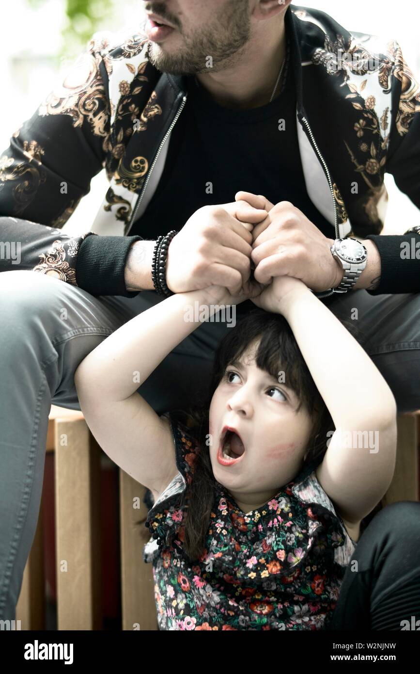 father holding hands of astonished daughter child yawning Stock Photo
