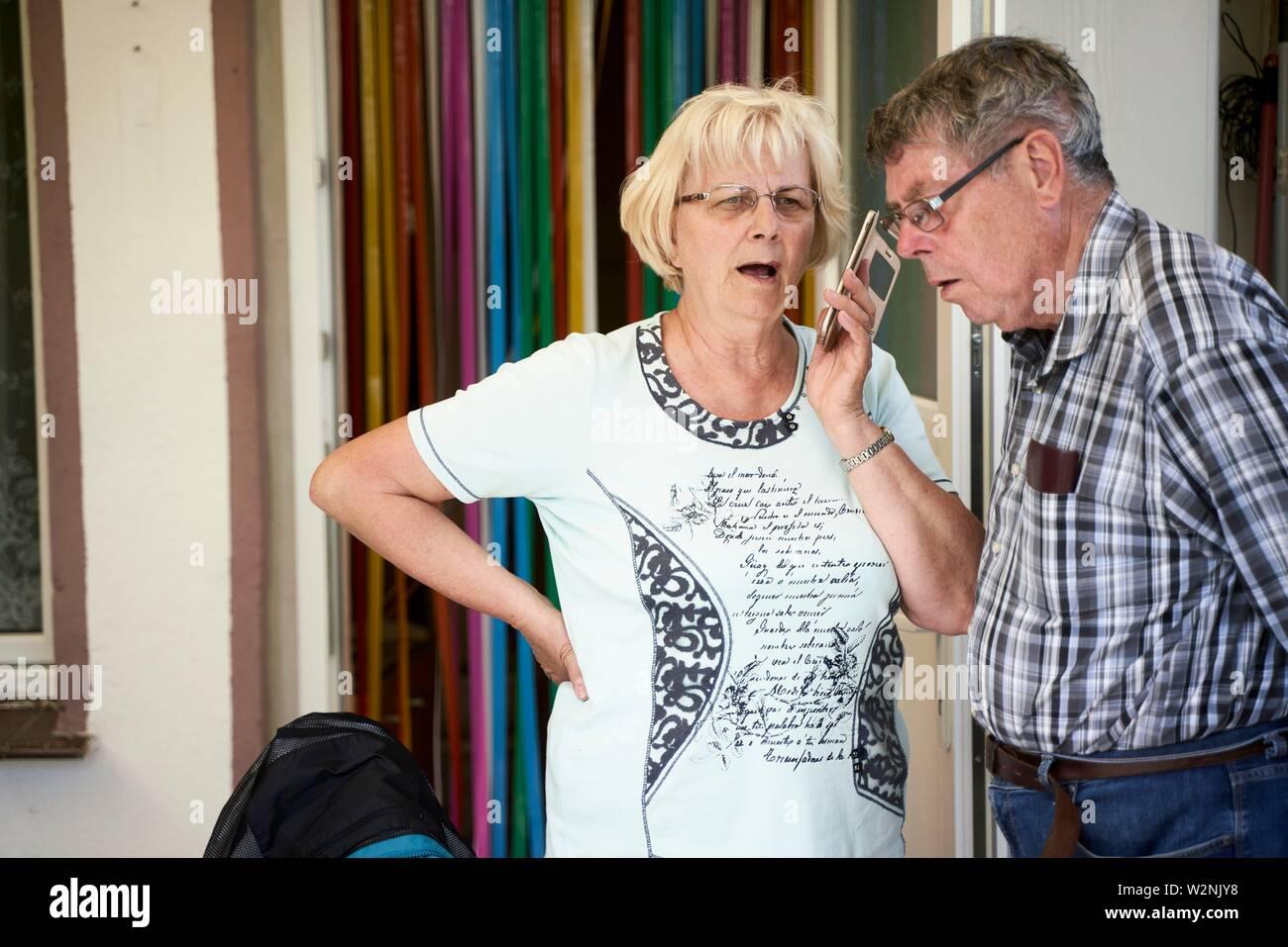 bigoted senior woman lamenting on phone conversation, husband listening - Stock Image