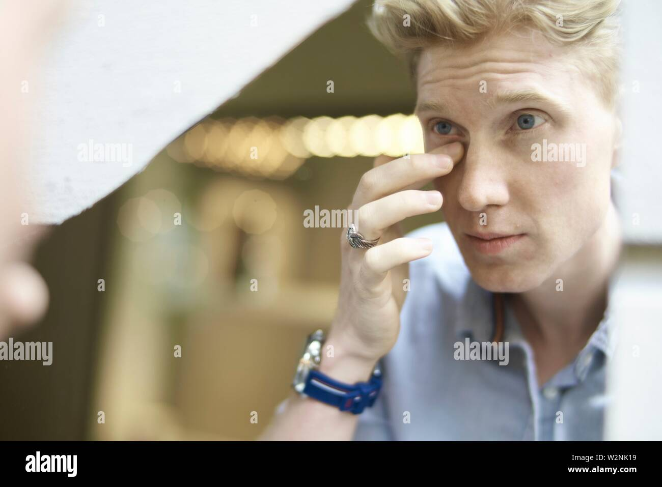 young man checking his appearance in mirror, eye circles - Stock Image