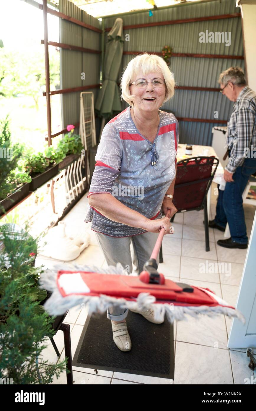 senior housewife woman with mop on terrace at allotment garden bungalow, cleaning - Stock Image