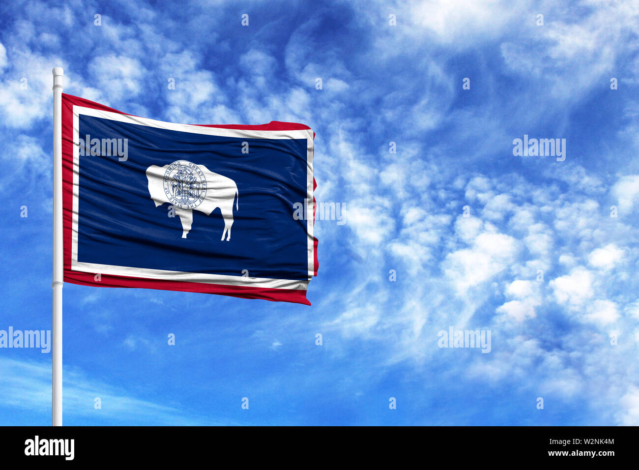 National flag State of Wyoming on a flagpole in front of blue sky - Stock Image