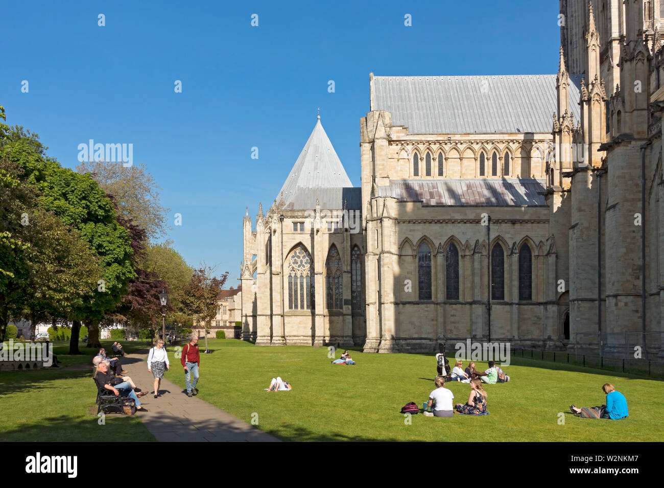 People enjoying the spring sunshine in Deans Park next to the Minster York North Yorkshire England UK United Kingdom GB Great Britain Stock Photo