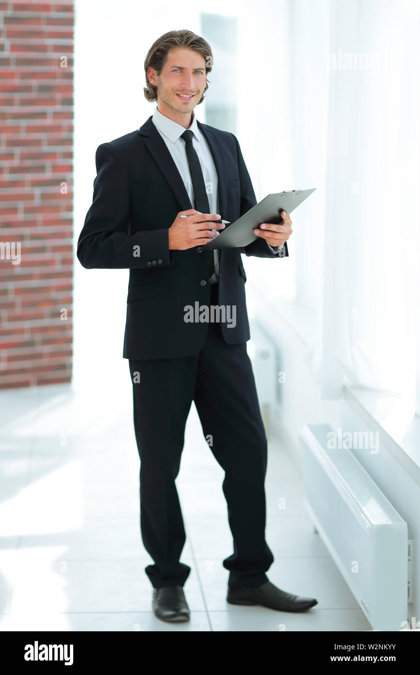 handsome businessman with business document standing in office - Stock Image