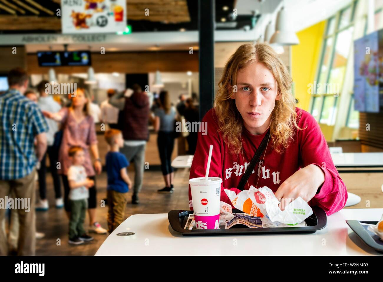 Berlin, Germany. Young adult, male music student eating an unhealthy set of hamburgers at the McDonalds fastfood restaurant during his lunchbreak. - Stock Image