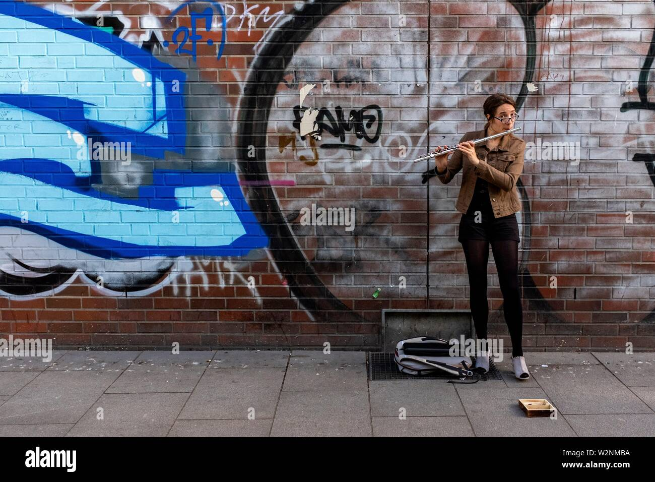 Berlin, Germany. Young woman playing classical music pieces on her flute, standing in front of a huge Graffity, earning a modest buck. - Stock Image