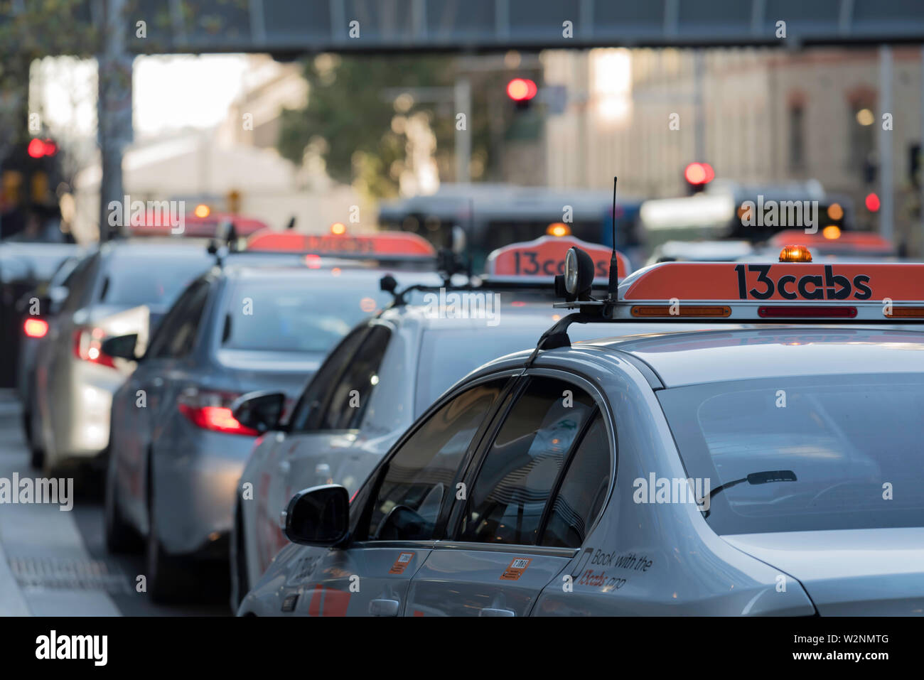 A line of taxis wait with their light on outside a building in Sydney in the early evening - Stock Image