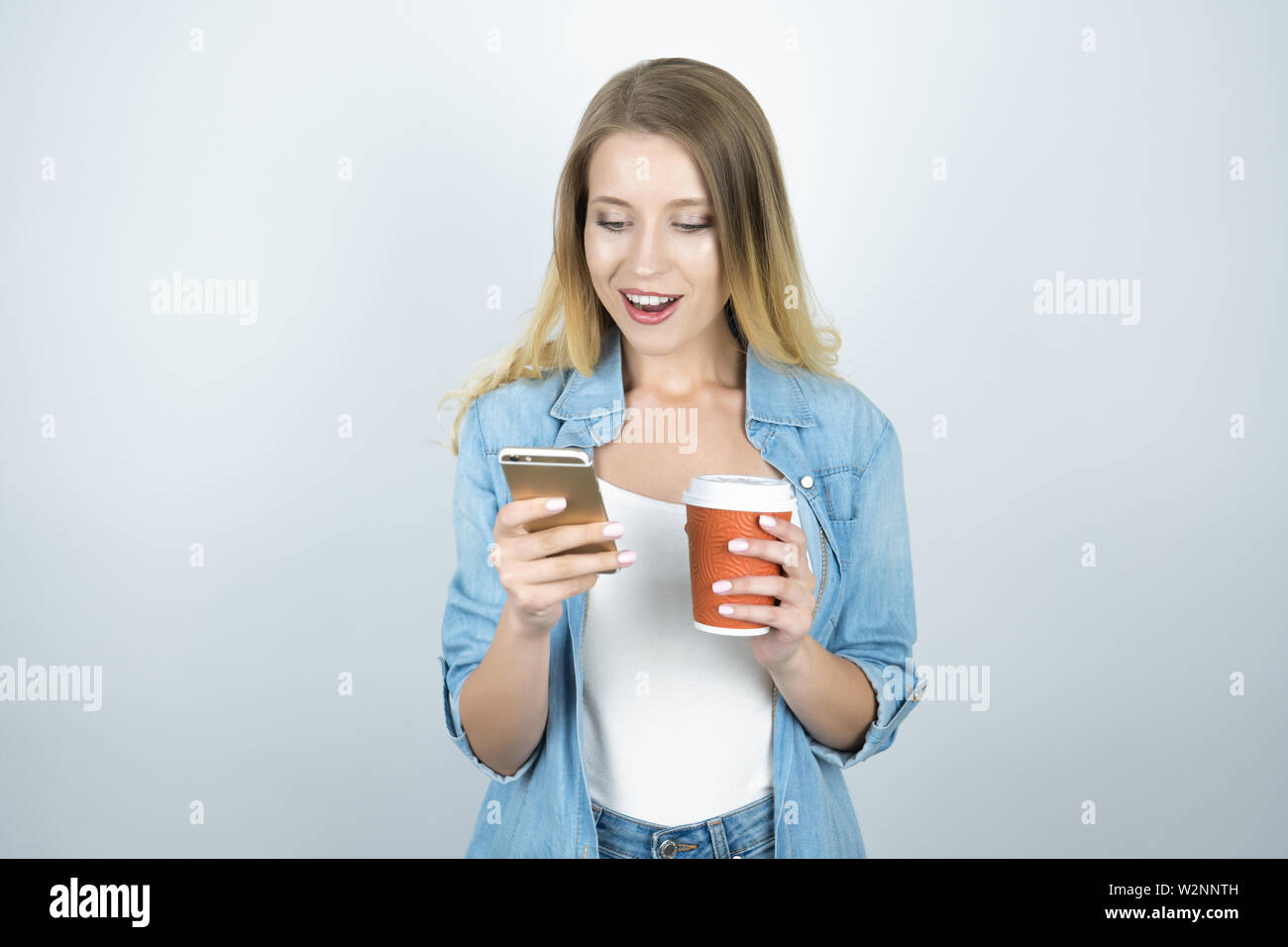 young happy blond woman holding smartphone in one hand and cup of coffee in another isolated white background - Stock Image