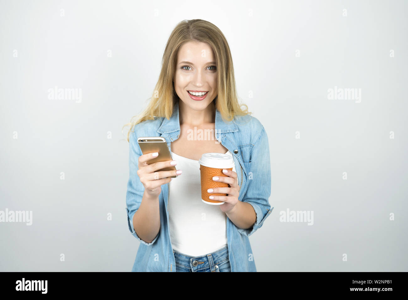 young blond woman smiling holding smartphone in one hand and cup of coffee in another isolated white background - Stock Image