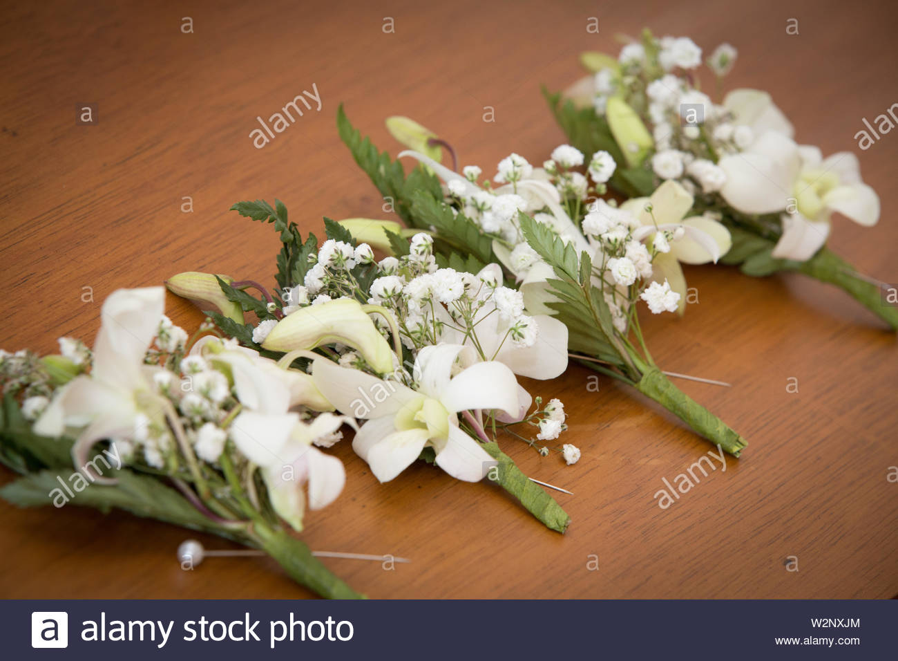 Best men boutonniere on a wooden table .  Wedding boutonniere detail shot. Groomsman concept. Beautiful white flowers bloomed boutonniere. Stock Photo