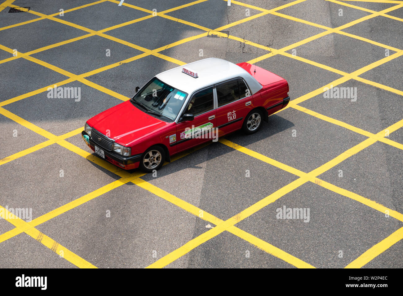 Red taxi in Hong Kong Island Drive through the middle of the intersection with the yellow line at the city center. - Stock Image