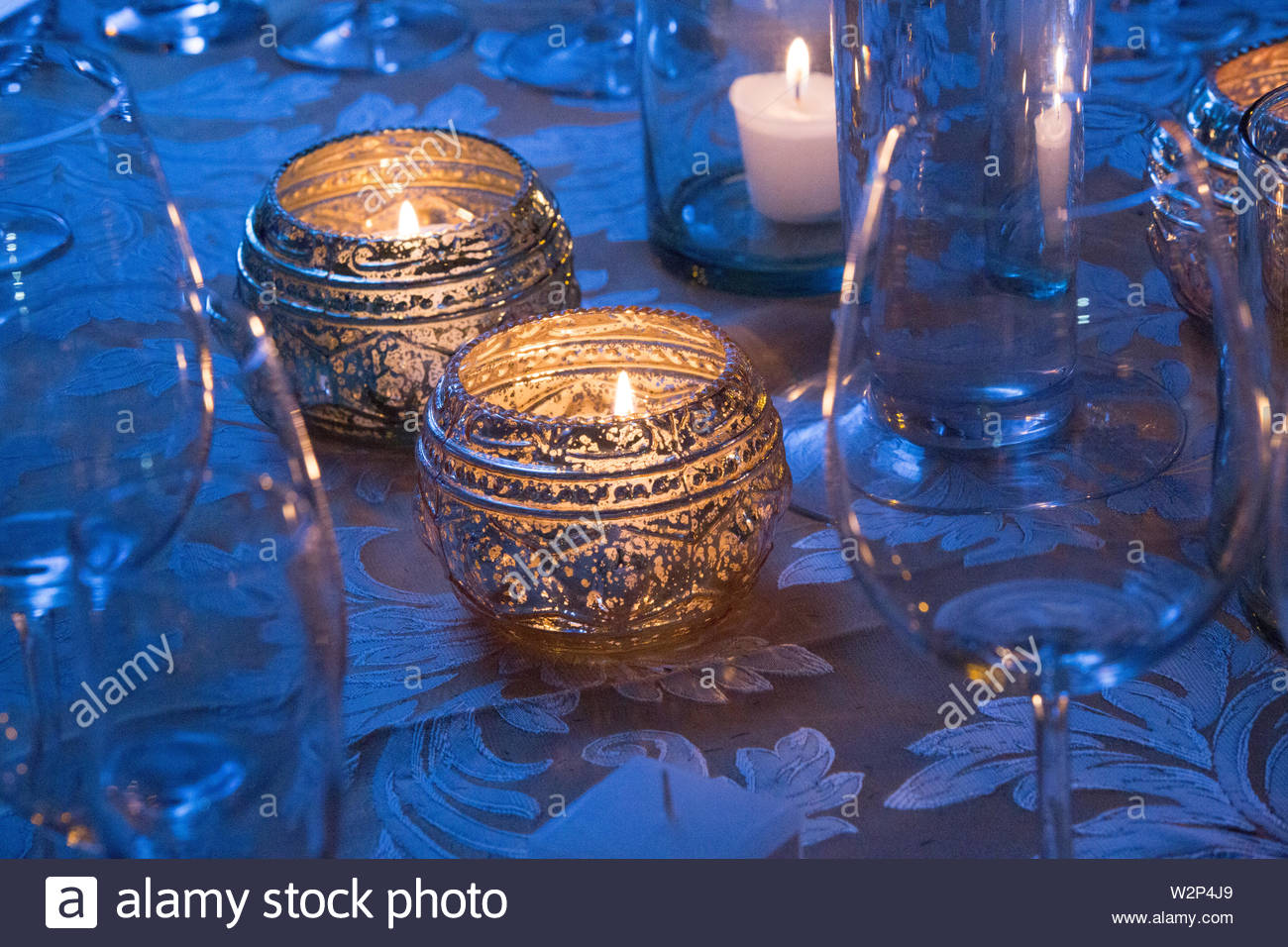 Christmas dinner table with candles and glassware. Preparation for holiday: Christmas and Hannukah dinner night. Concept family dinner on special occa - Stock Image