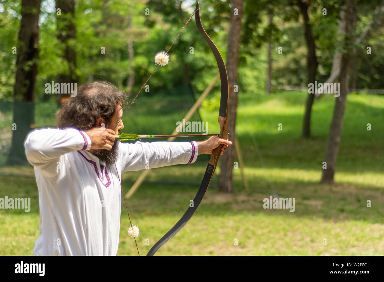 Nis, Serbia - June 16. 2019 Archer with bow shoot arrow in the forest on knight festival and tournament in a traditional suit. Bowman before shooting - Stock Image