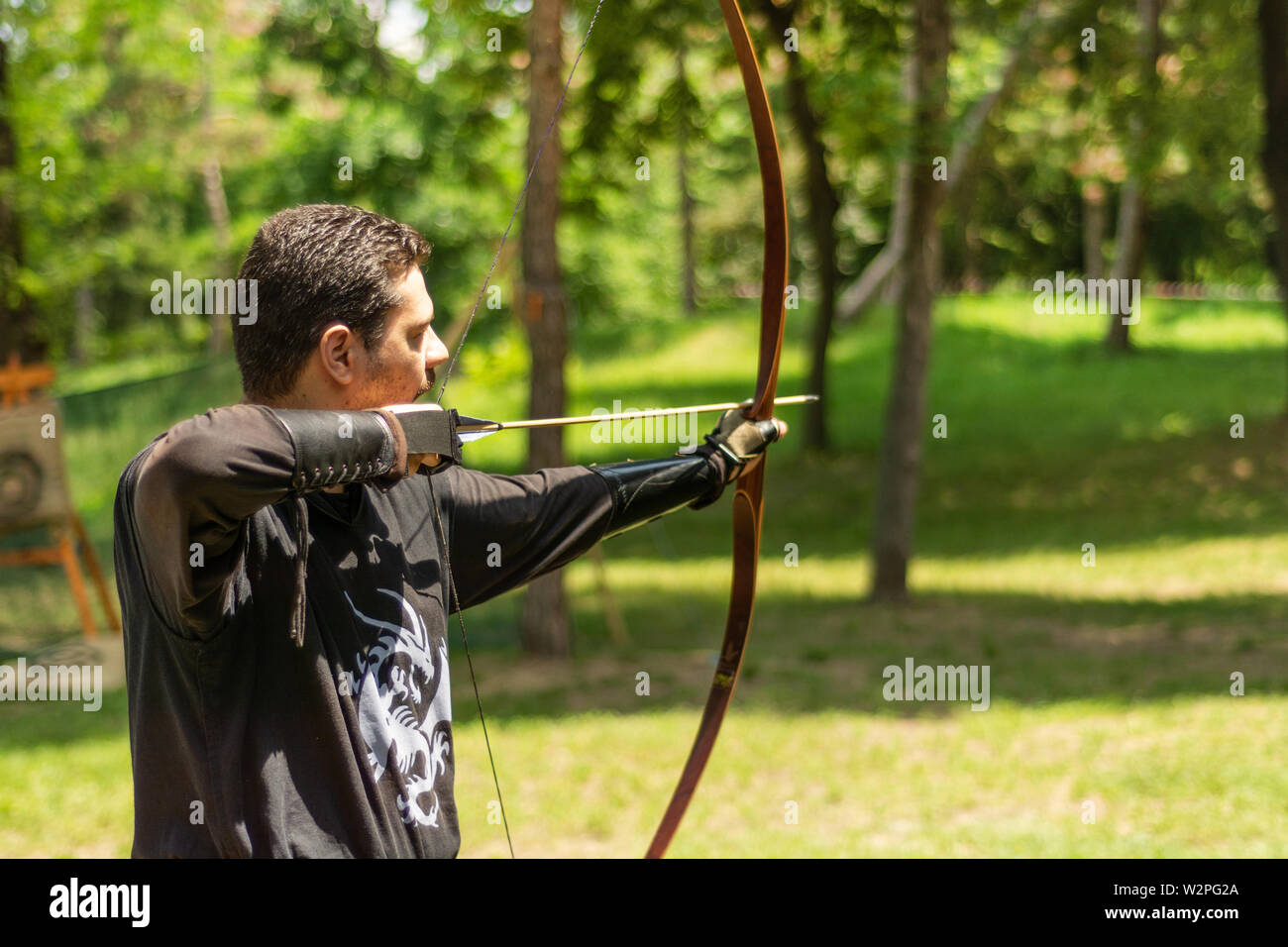 Nis, Serbia - June 16. 2019 Archer with bow shoot arrow in the forest on knight festival in a traditional suit. Bowman before shooting from a longbow - Stock Image