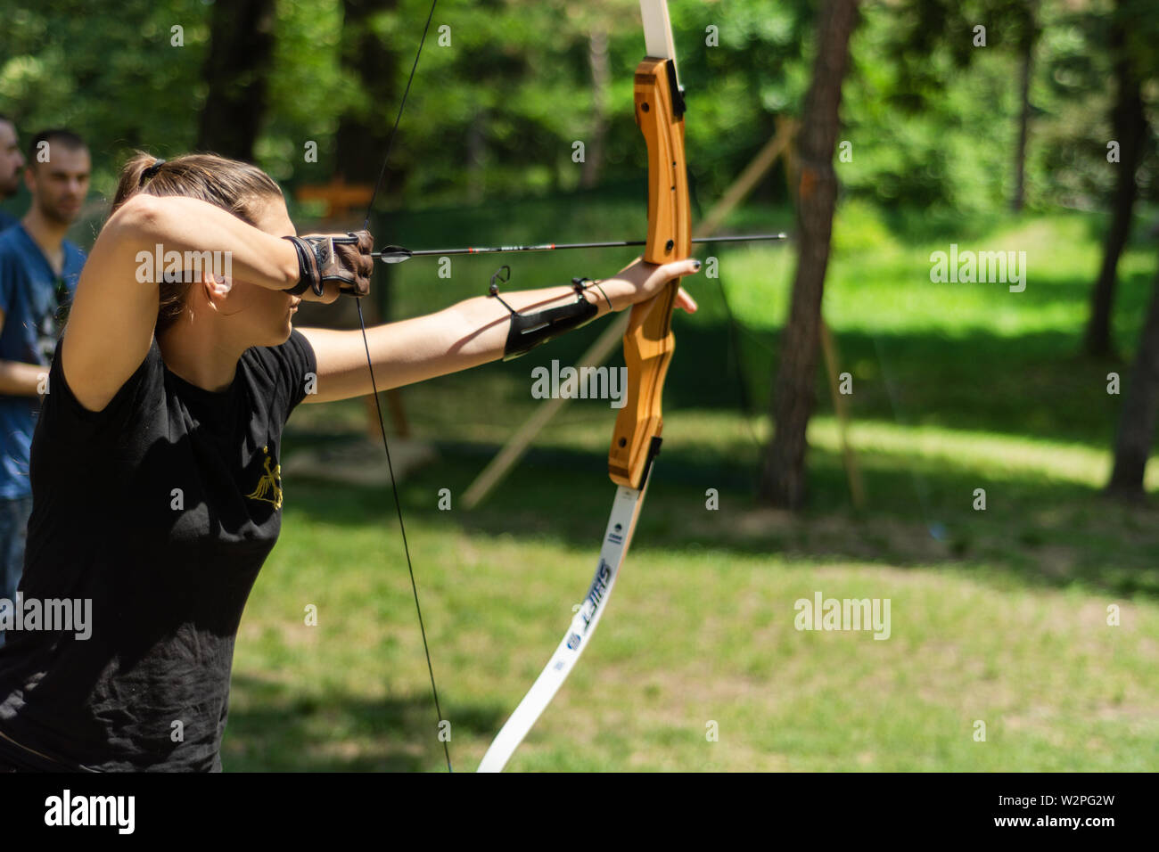 Nis, Serbia - June 16. 2019 Professional girl archer with bow shoot arrow in the forest on knight festival and tournament. Bowman before shooting - Stock Image