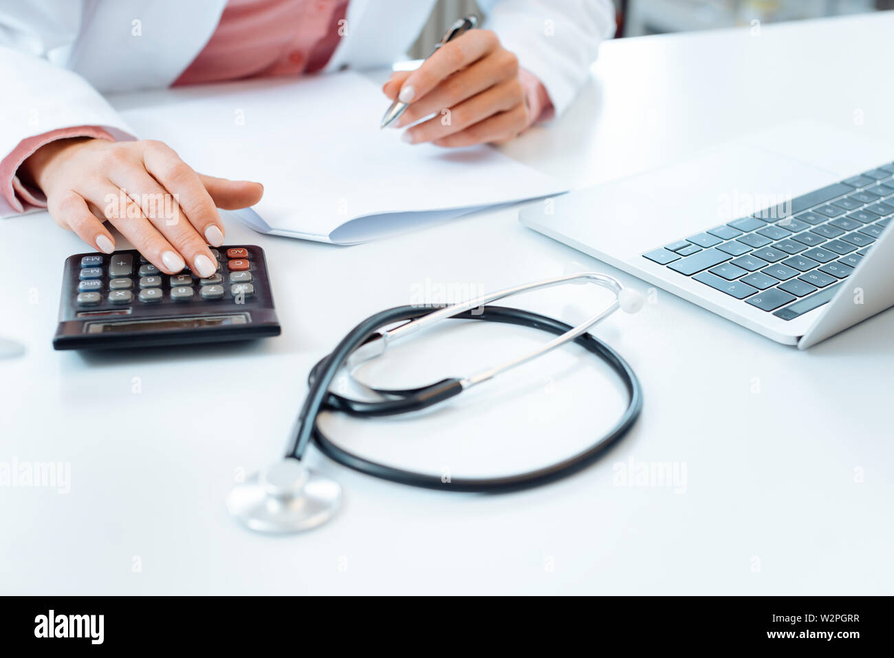 Doctor using calculator writing bills and doing bookkeeping - Stock Image