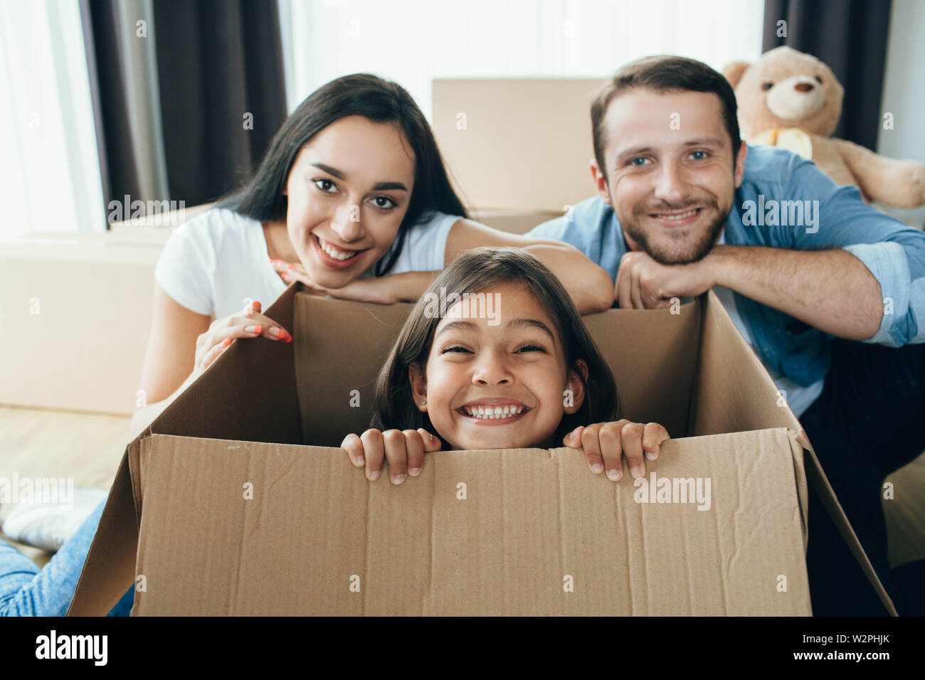 Cute little girl sitting in carton boxes , playing with her parent while moving into new home Stock Photo