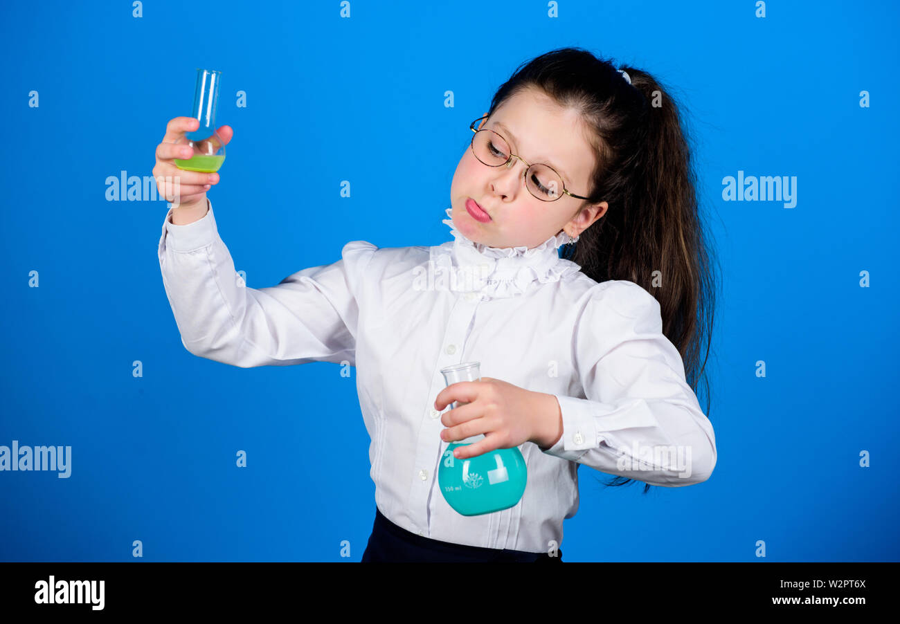 back to school. child study bilogy lesson. science research in lab. Small school girl. education and knowledge. small smart girl with testing flask. This is what we are testing today. - Stock Image