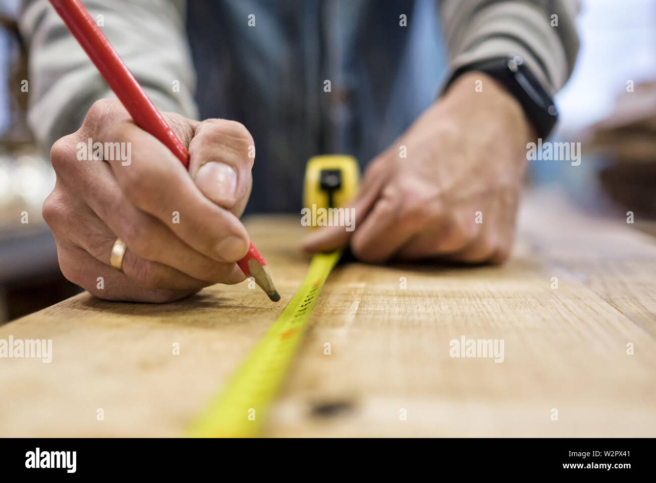 Carpenter measuring and tracing line with a ruler and pencil on wooden timber. - Stock Image
