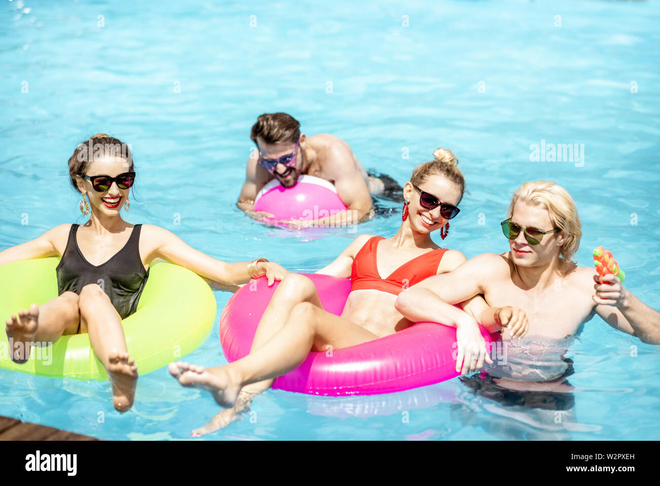 Group of a happy friends having fun, swimming with inflatable toys in the swimming pool outdoors during the summertime Stock Photo