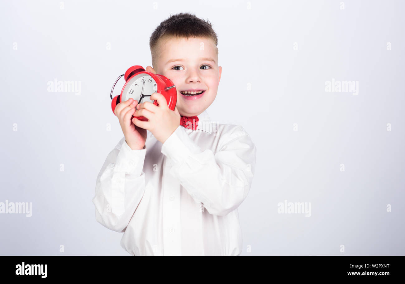 Time management. Morning. little boy with alarm clock. Time to relax. Party time. Businessman. Formal wear. tuxedo kid. Happy childhood. happy child with retro clock in bow tie. Morning inspiration. - Stock Image