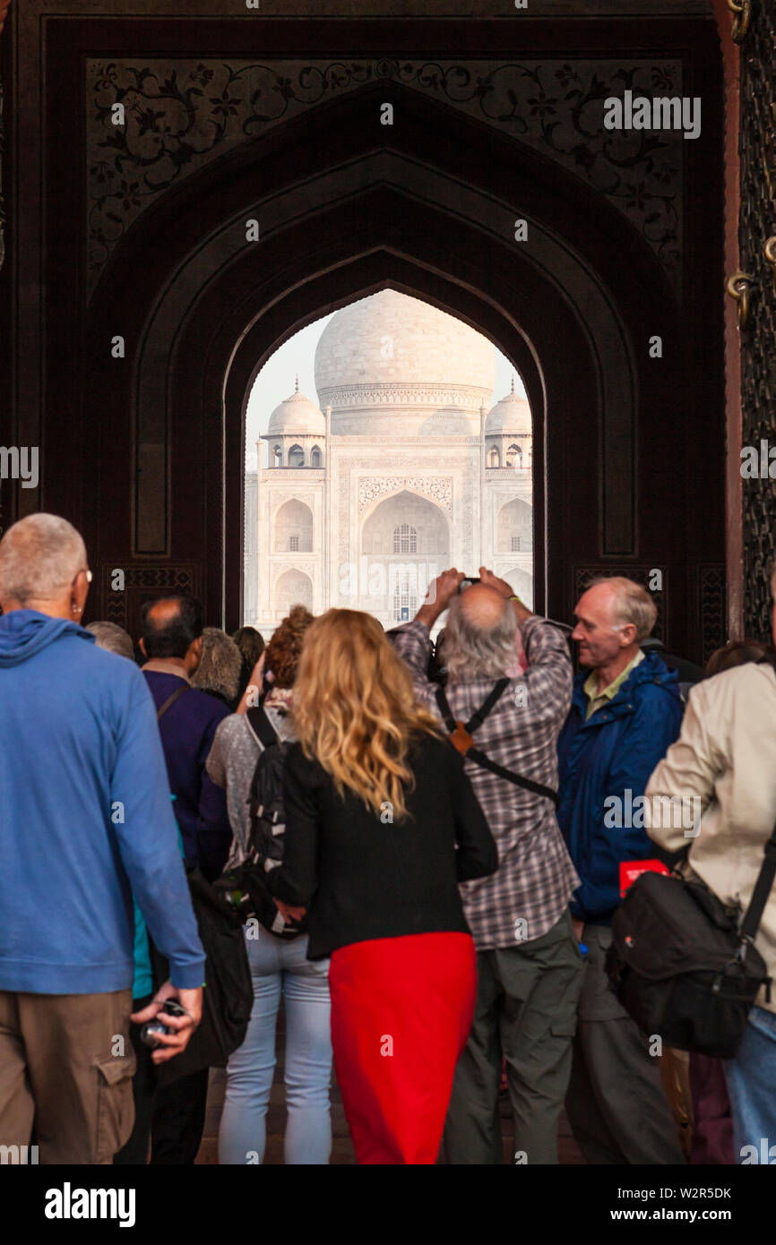 Looking through the main entrance gate at The Taj Mahal in Agra, India with tourists taking pictures in the foreground. - Stock Image